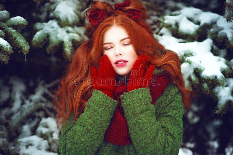 Schönes rotes behaartes Mädchen mit der kreativen Frisur, die mit geschlossenen Augen vor Schnee aufwirft, bedeckte Tannenbäume stockbild