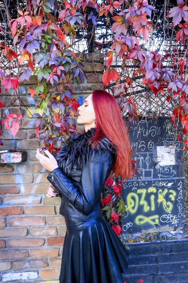 Schönes rotes Hauptmädchen, das schwarze lederne Ausstattung trägt und Herbstlaub vor einer Backsteinmauer riecht und genießt stockfotografie