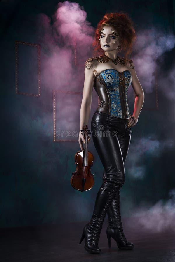 Schönes Rothaarige cosplayer Mädchen, das ein steampunk Korsett und ledernen Hosen mit einer großen Brust trägt, hält Violine in  stockfotos