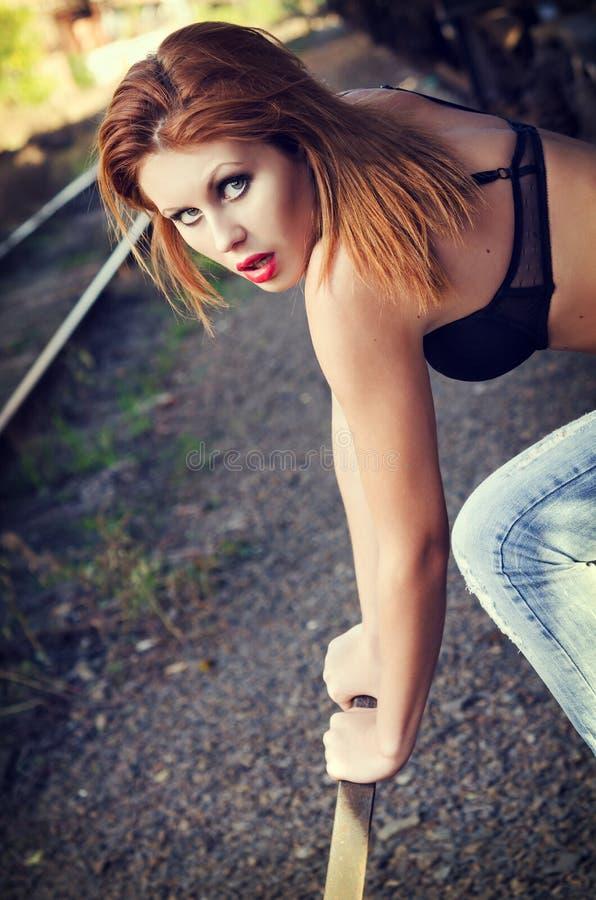 Schönes Rothaarigemädchen im BH und in den Jeans zieht einen Bahnhebel nahaufnahme lizenzfreies stockfoto