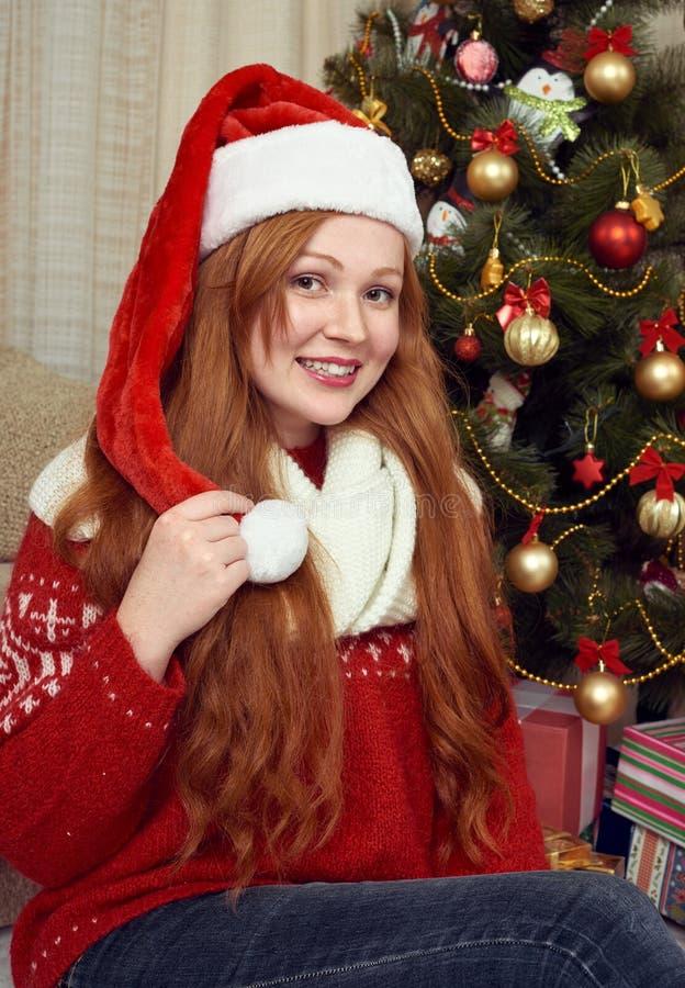 Schönes Rothaarigemädchenporträt in der Weihnachtsdekoration Ausgangsinnenraum mit Tannenbaum und -geschenken Sylvesterabend und  lizenzfreies stockbild
