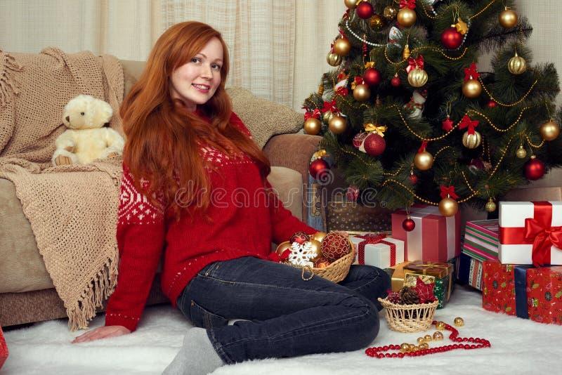 Schönes Rothaarigemädchenporträt in der Weihnachtsdekoration Ausgangsinnenraum mit Tannenbaum und -geschenken Sylvesterabend und  stockbild