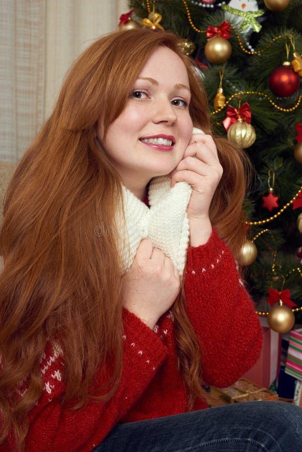 Schönes Rothaarigemädchenporträt in der Weihnachtsdekoration Ausgangsinnenraum mit Tannenbaum und -geschenken Sylvesterabend und  lizenzfreie stockfotos