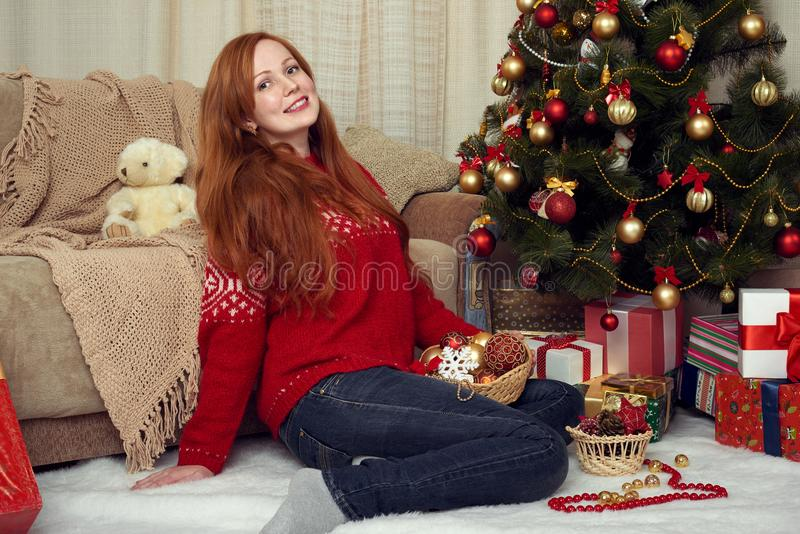 Schönes Rothaarigemädchenporträt in der Weihnachtsdekoration Ausgangsinnenraum mit Tannenbaum und -geschenken Sylvesterabend und  lizenzfreies stockfoto