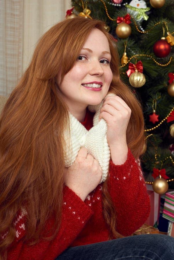 Schönes Rothaarigemädchenporträt in der Weihnachtsdekoration Ausgangsinnenraum mit Tannenbaum und -geschenken Sylvesterabend und  stockfotos