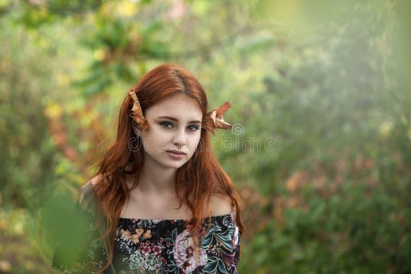 Schönes rothaariges junges Mädchen mit einem reizend Blick und einem Herbst lizenzfreie stockfotografie