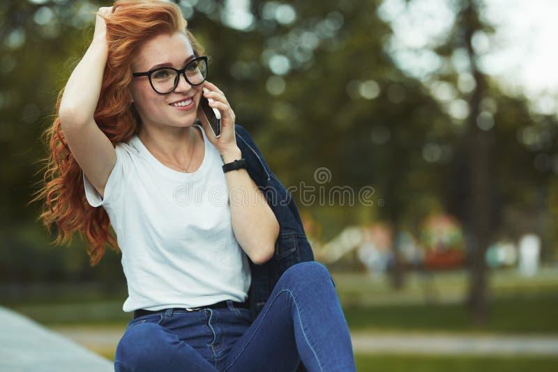 Schönes rothaariges Mädchen mit einer schönen Zahl und ein Telefon in ihren Händen Das Mädchen verständigt sich auf ihrem moderne lizenzfreies stockfoto