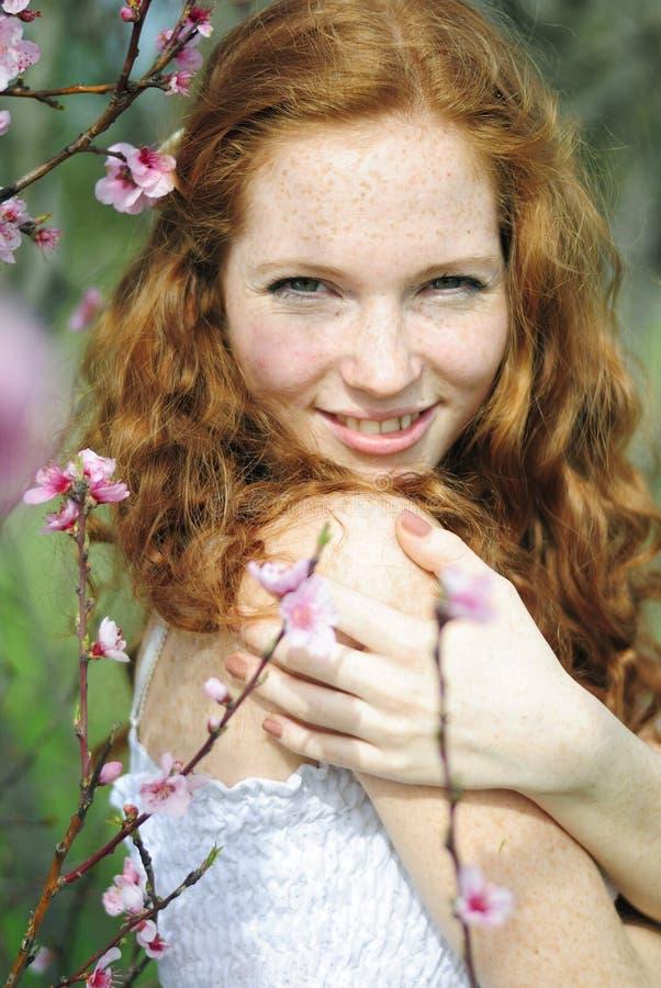 Schönes rothaariges Mädchen unter den blühenden Bäumen lizenzfreie stockfotografie