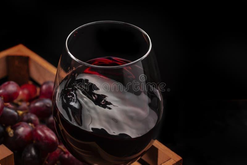 Schönes Rotweinspritzen in einem Glasbecher in einer Holzkiste mit Trauben, schwarzer Hintergrund stockbild