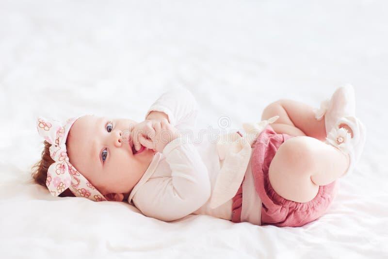 Schönes Säuglingsbaby haftet Finger in den Mund, die Babydentition, itching gummiert stockfoto