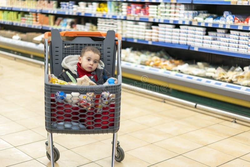 Schönes Schätzchen im Einkaufswagen - Laufkatze Eine Laufkatze mit Produkten, in denen das Kind sitzt Voller Warenkorb mit Lebens lizenzfreies stockfoto