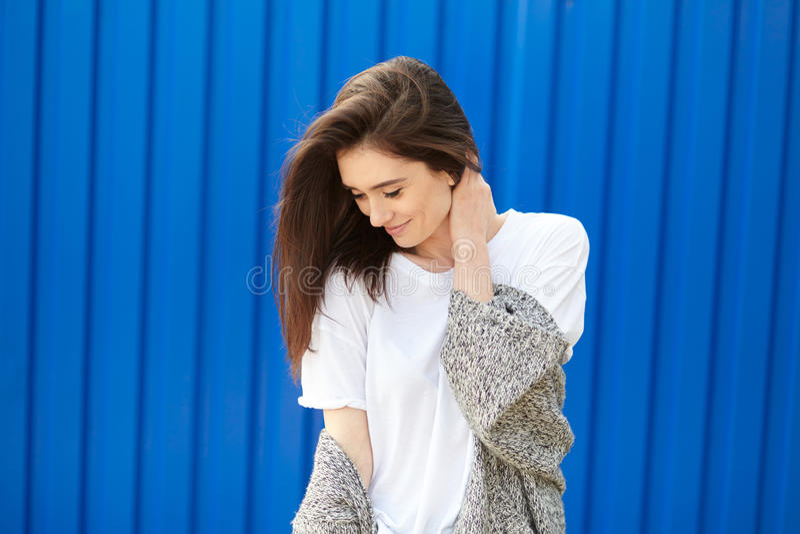 Schönes schüchternes Mädchen, das auf einem blauen Hintergrund lächelt stockfoto