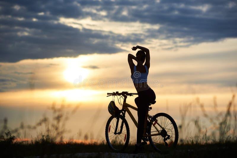 Schönes Schattenbild der hinteren Ansicht der perfekten Körperfrau gegen den Hintergrundabendhimmel mit untergehender Sonne stockfoto