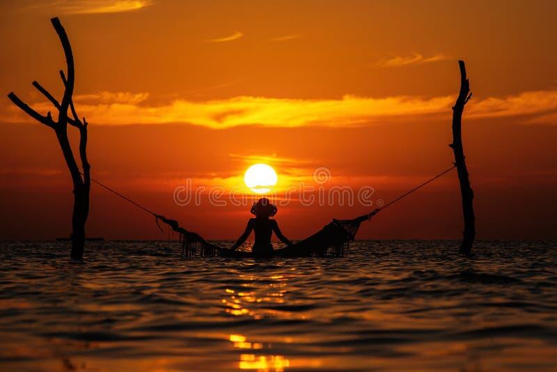Schönes Schattenbild der jungen Frau mit dem Schwingen, das im Meer auf Sonnenuntergang, maledivische romantische Landschaft auf stockfotos