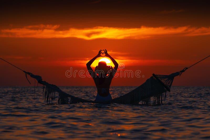 Schönes Schattenbild der jungen Frau mit dem Schwingen, das im Meer auf Sonnenuntergang, maledivische romantische Landschaft auf lizenzfreie stockbilder