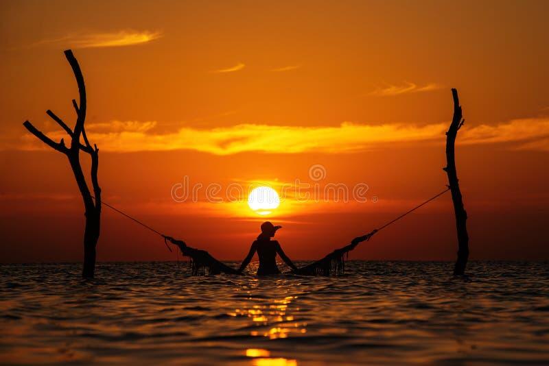 Schönes Schattenbild der jungen Frau mit dem Schwingen, das im Meer auf Sonnenuntergang, maledivische romantische Landschaft auf stockfoto