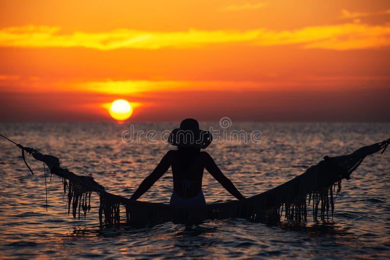 Schönes Schattenbild der jungen Frau mit dem Schwingen, das im Meer auf Sonnenuntergang, maledivische romantische Landschaft auf lizenzfreie stockfotografie