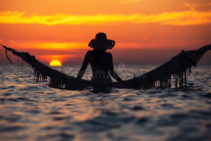 Schönes Schattenbild der jungen Frau mit dem Schwingen, das im Meer auf Sonnenuntergang, maledivische romantische Landschaft auf stockbilder