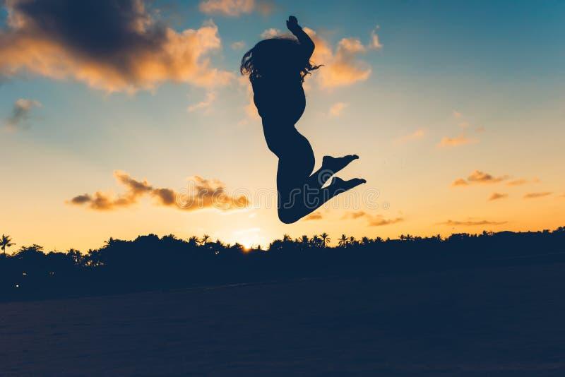 Schönes Schattenbildporträt des Sommermädchens springend auf weißen Sand in der exotischen Insel bei Sonnenuntergang Ruhe, Entspa lizenzfreie stockfotografie