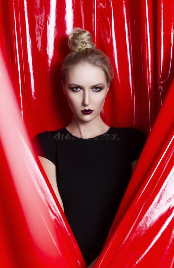 Schönes schlankes blondes Mädchen gekleidet in einem schwarzen passenden Kleid auf einem Hintergrund des roten Latexgewebes Moder lizenzfreie stockfotografie