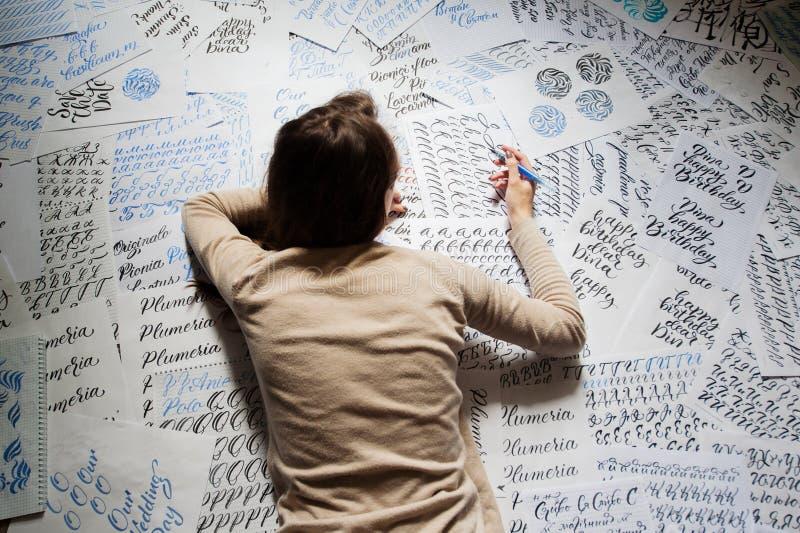 Schönes Schreibkünstlerschreiben der jungen Frau etwas, das auf dem Boden am Wohnzimmer liegt lizenzfreies stockfoto