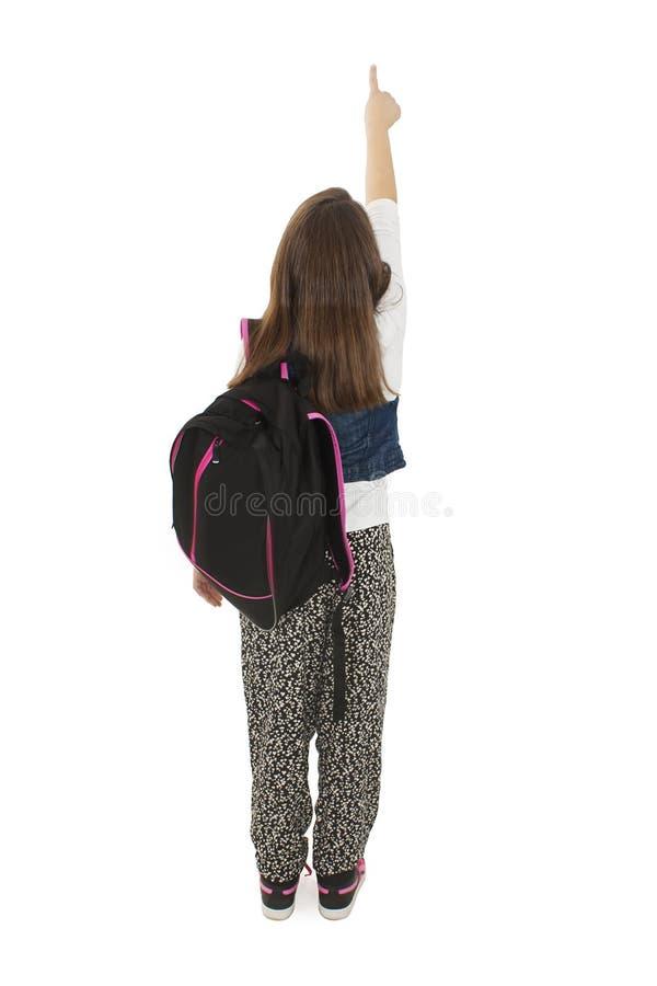 Schönes Schulmädchen mit Rucksäcken zeigend auf Wand Rückseitige Ansicht stockfotos