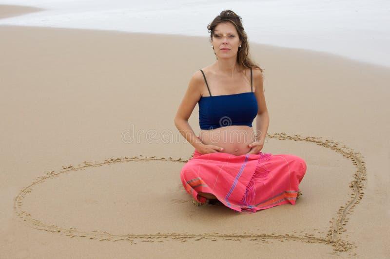 Schönes schwangeres Mädchen auf dem Strand stockfoto