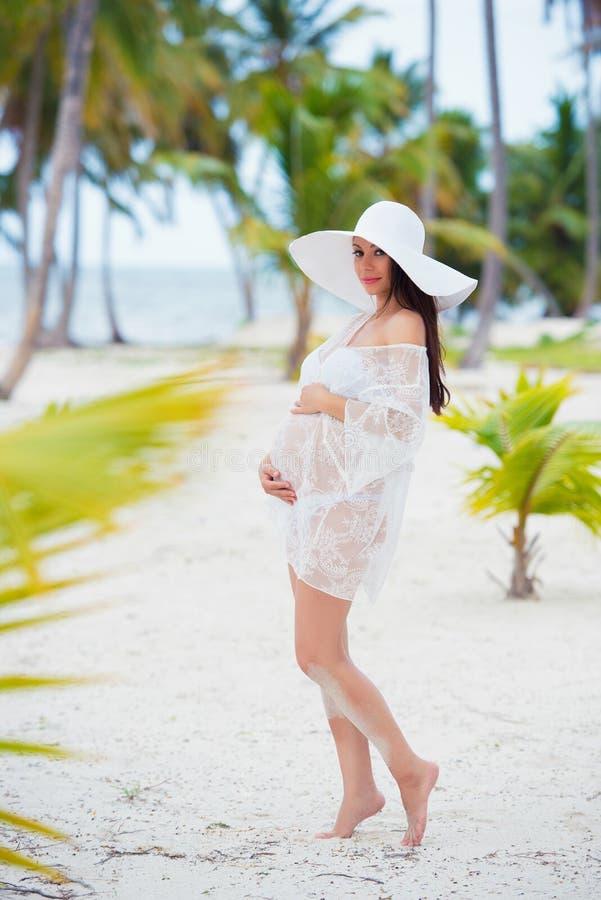 Schönes schwangeres Mädchen im weißen Kleid und im breitrandigen Hut auf Strand nahe Palmen stockfotografie