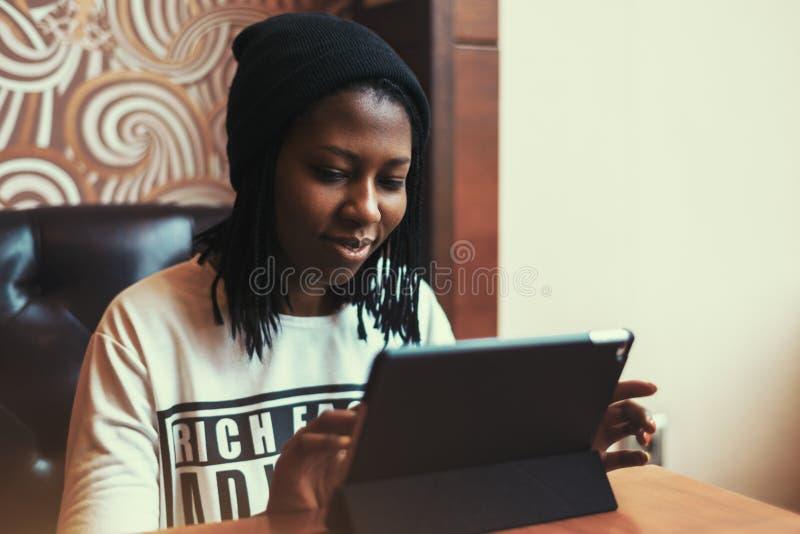 Schönes schwarzes Mädchen, das an Tablette im Café lächelt und arbeitet stockbilder