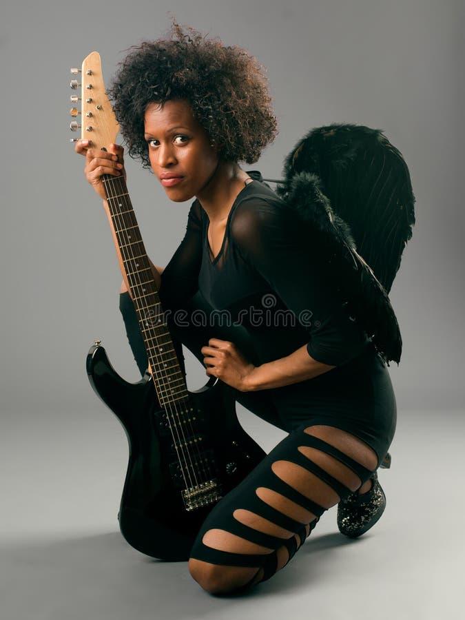Schönes schwarzes Mädchen mit Engelsflügeln und -E-Gitarre stockfoto