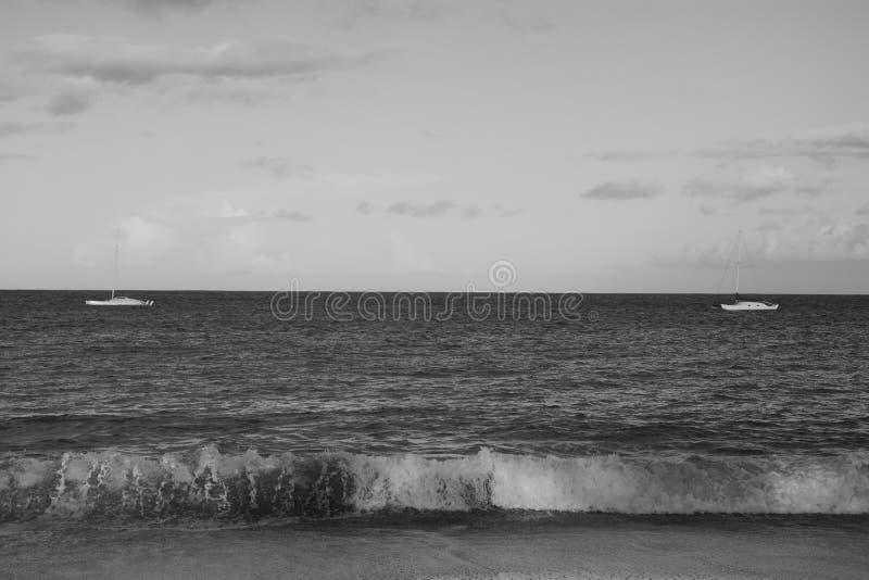 Schönes Schwarzweiss-Bild von Meereswogen mit zwei Booten lizenzfreie stockfotografie