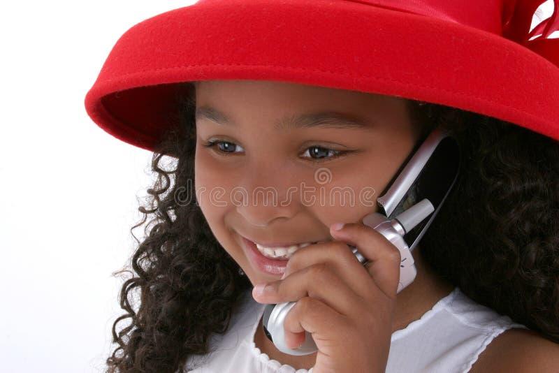 Schönes sechs Einjahresmädchen in Red Hat mit Mobiltelefon lizenzfreie stockfotografie