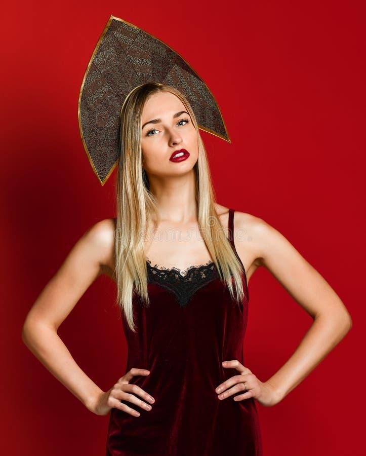 Schönes sexy blondes russisches Mädchen in traditionellem kokoshnik Hut, festliches Kleid des Samts auf einem roten Hintergrund, lizenzfreies stockfoto