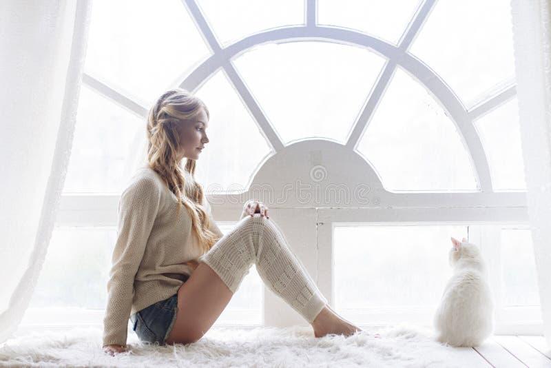 Schönes sexy blondes Sitzen im Fenster zusammen mit der Katze lizenzfreie stockfotografie