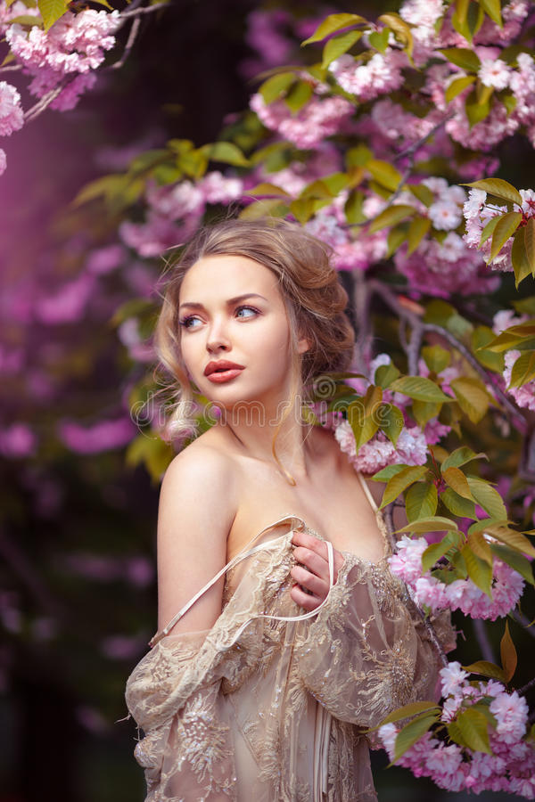 Schönes sexy erwachsenes Mädchen, das an blühendem Baum im Garten steht lizenzfreie stockbilder