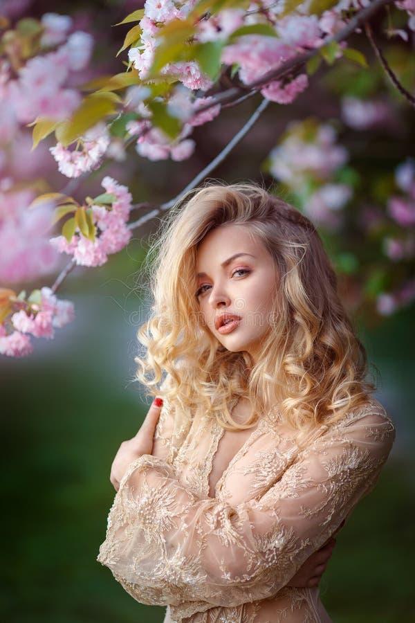 Schönes sexy erwachsenes Mädchen, das an blühendem Baum im Garten steht lizenzfreies stockbild