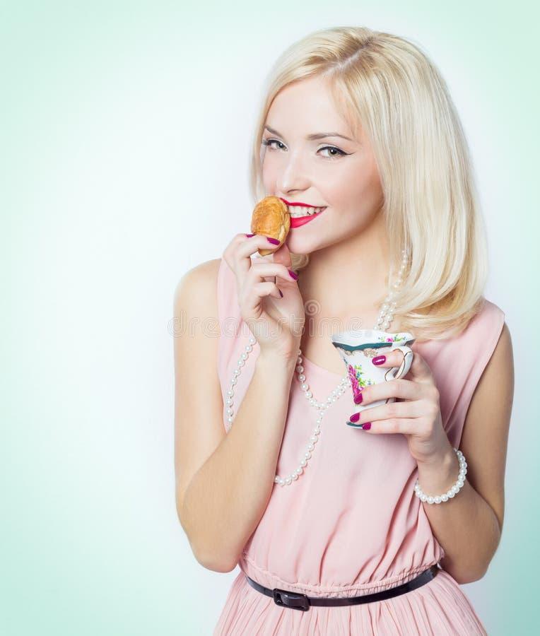 Schönes sexy herrliches blondes Mädchen mit hellem Make-up im rosa Kleid im Studio auf einem weißen Hintergrundsitzen lizenzfreie stockfotografie