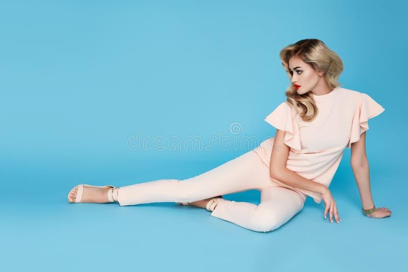 Schönes sexy junges blondes Haar der Geschäftsfrau mit dem Abendmake-up, das eine Smokingspitze und einen Stöckelschuhgeschäftsst stockfoto