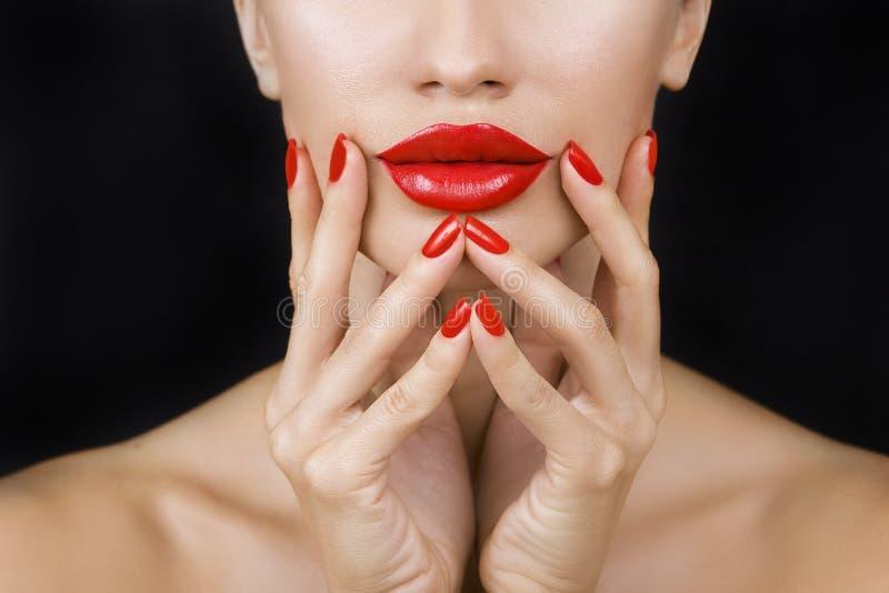 Schönes sexy junges Mädchen mit den roten Lippen und rotem Nagellack lizenzfreie stockbilder