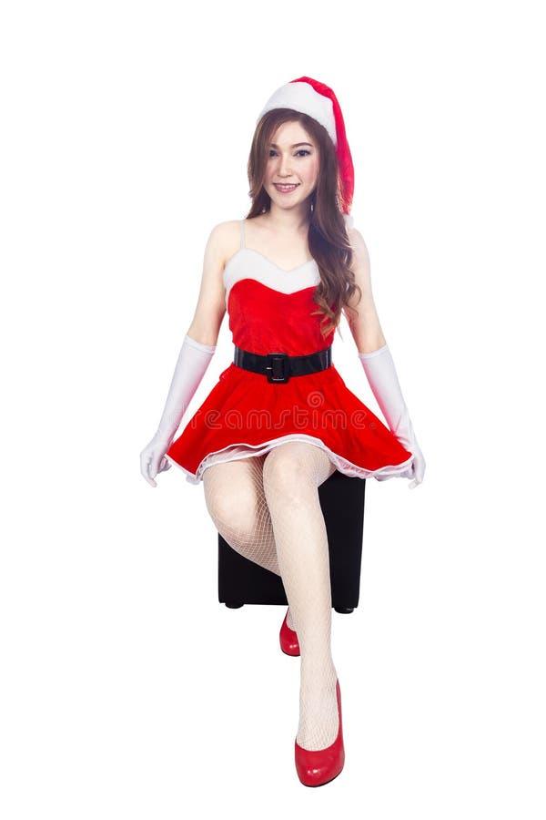 Schönes sexy Mädchen, das Weihnachtsmann-Kleidung trägt und Isolator sitzt lizenzfreies stockbild