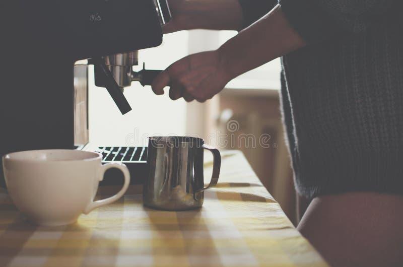 Schönes sexy Mädchen in der Strickjacke macht Kaffee zu Hause stockbilder