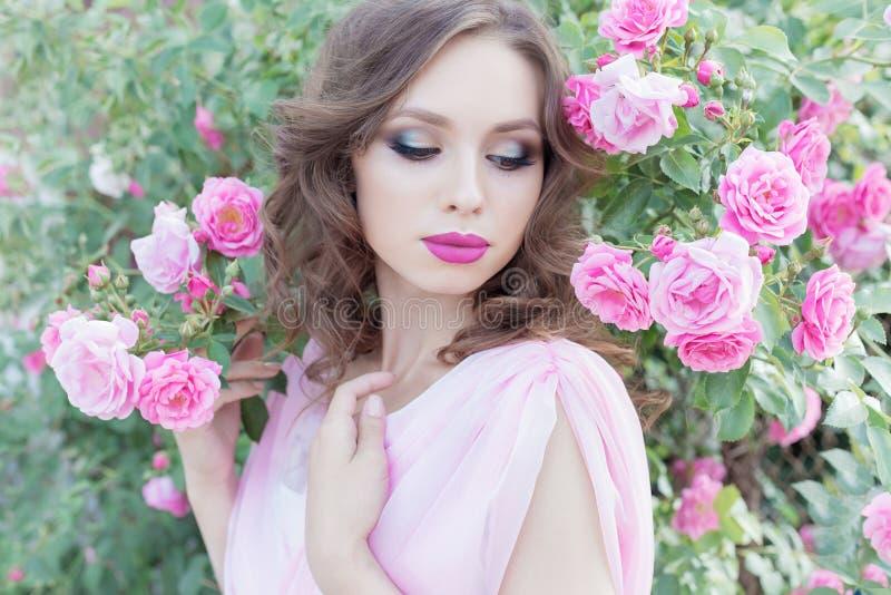 Schönes sexy Mädchen in einem rosa Kleid, das in den Gartenrosen an einem sonnigen hellen Sommertag mit einem leichten Make-up un stockbilder