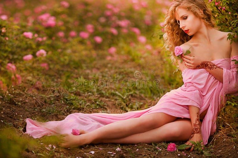 Schönes sexy Mädchen in einem rosa Kleid, das in den Gartenrosen steht stockfoto