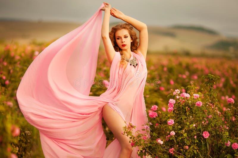Schönes sexy Mädchen in einem rosa Kleid, das in den Gartenrosen steht lizenzfreie stockfotografie
