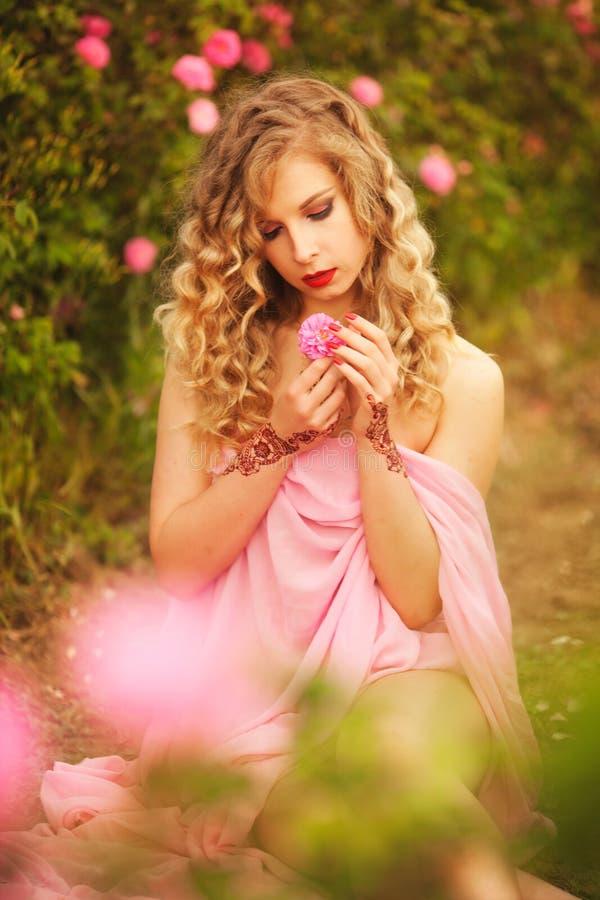 Schönes sexy Mädchen in einem rosa Kleid, das in den Gartenrosen steht lizenzfreies stockbild