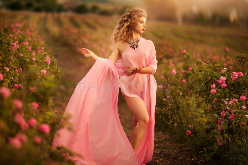 Schönes sexy Mädchen in einem rosa Kleid, das in den Gartenrosen steht lizenzfreie stockfotos