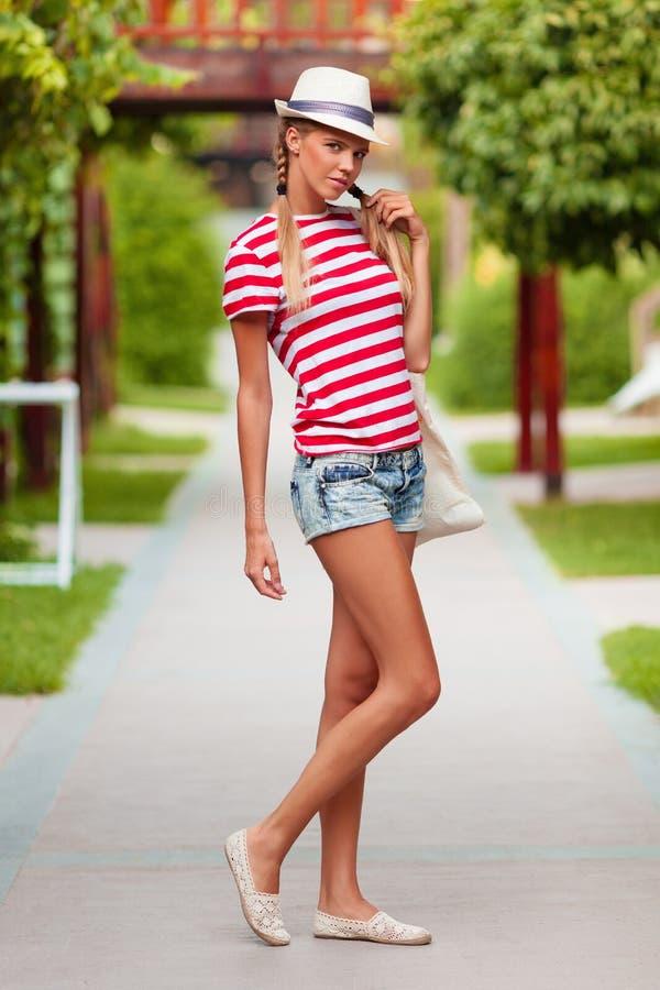 Schönes sexy Mädchen kurz gesagt und gestreiftes T-Shirt, im Hut, draußen Gebräuntes Mädchen im Sommer stockfotografie