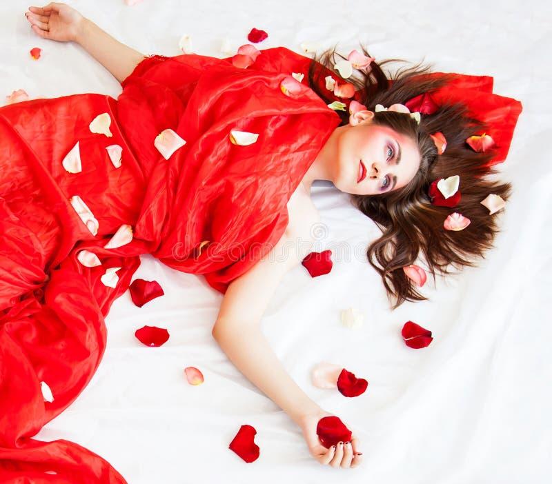 Schönes sexy Mädchen mit dem langen Haar, das auf weißen Blättern mit den rosafarbenen Blumenblättern sich entspannt stockbilder