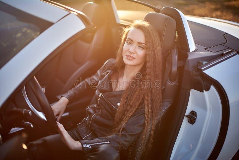 Schönes sexy Mädchen mit dem langen Haar in einer Lederjacke und den Lederhosen in der Sonnenbrille verlässt ein Auto bei Sonnenu stockfoto
