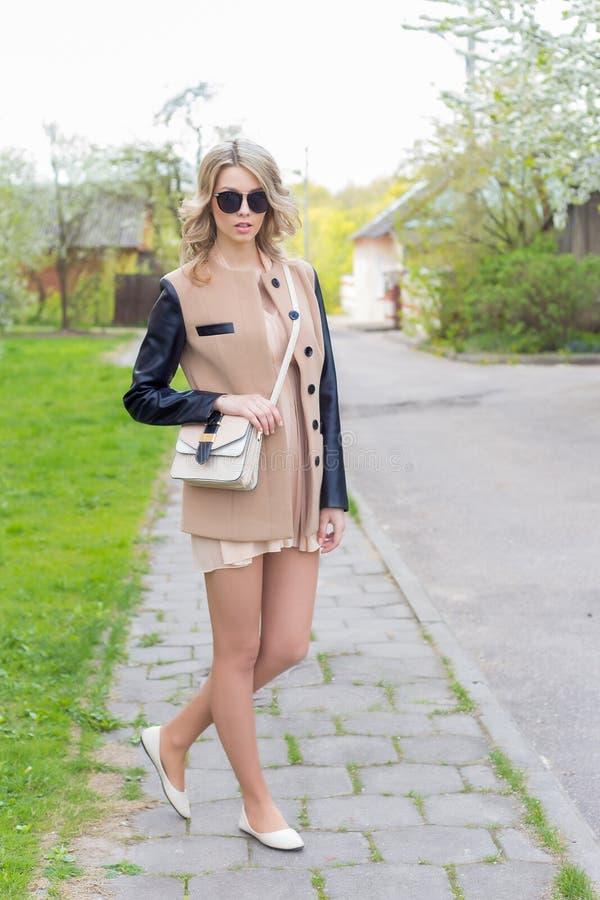 Schönes sexy Mädchen mit den vollen Lippen geht in Sonnenbrille in einem Mantel mit einer Handtasche durch die Stadtstraßen lizenzfreies stockbild